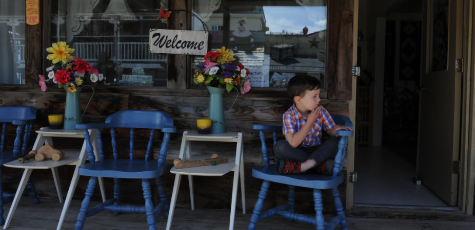 Kid sitting outside of a cafe in Stettler